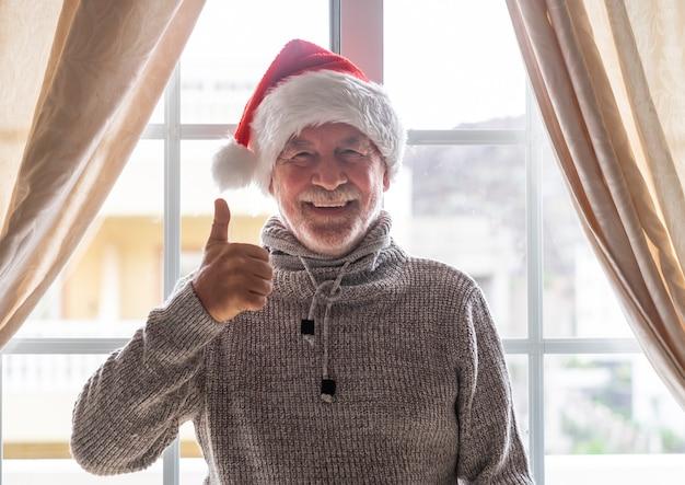 Ritratto di un uomo anziano con maglione invernale e cappello da babbo natale che resta a casa dietro la finestra