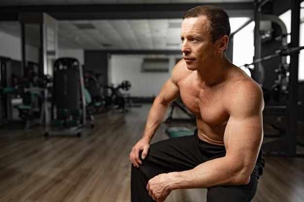 Ritratto di un uomo muscoloso anziano in una palestra