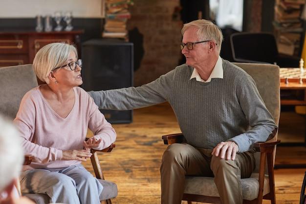 Ritratto di persone anziane che si sostengono a vicenda durante la sessione di terapia nello spazio della copia della casa di riposo