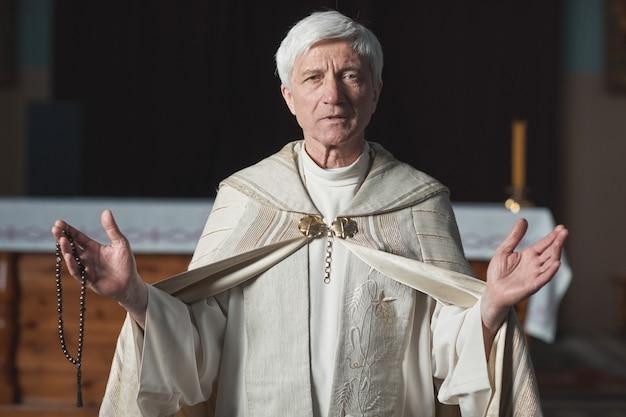 Ritratto di un sacerdote anziano in costume formale che guarda la telecamera e tiene il matrimonio in chiesa