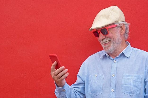 Ritratto di uomo anziano dai capelli bianchi con berretto che sorride usando il suo smartphone, in piedi su sfondo rosso red