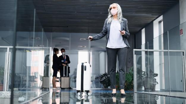 Ritratto di donna anziana nella lounge dell'aeroporto, coronavirus, viaggi e nuova normalità.