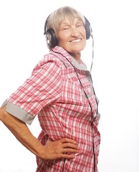 Ritratto di donna anziana che ascolta musica isolata su bianco