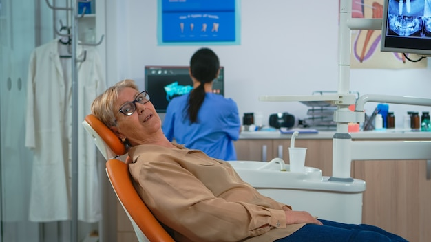 Ritratto di donna anziana che guarda la telecamera in attesa di uno stomatologo in clinica odontoiatrica. paziente anziano sdraiato su una sedia stomatologica che sorride alla webcam mentre l'infermiera lavora al computer in background.