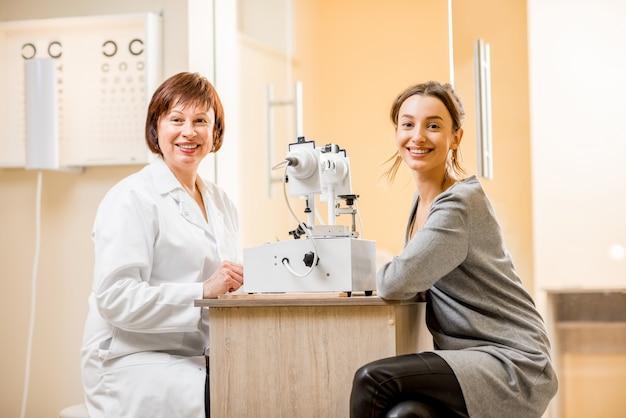 Ritratto di donna anziana oculista con la giovane paziente seduta nell'ufficio oftalmologico