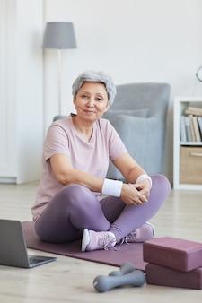 Ritratto della donna maggiore che si siede sulla stuoia di esercitazione