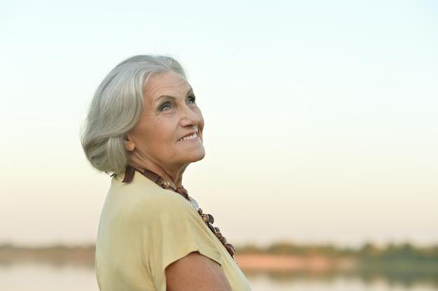 Ritratto di donna anziana in campo estivo
