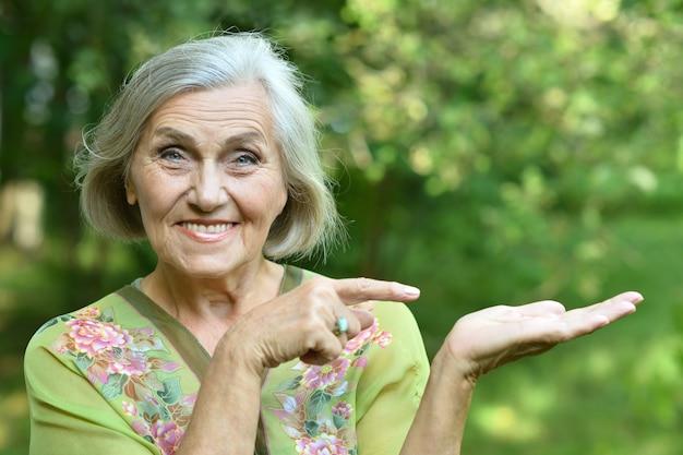 Ritratto di una donna anziana nel parco estivo che mostra lo spazio della copia