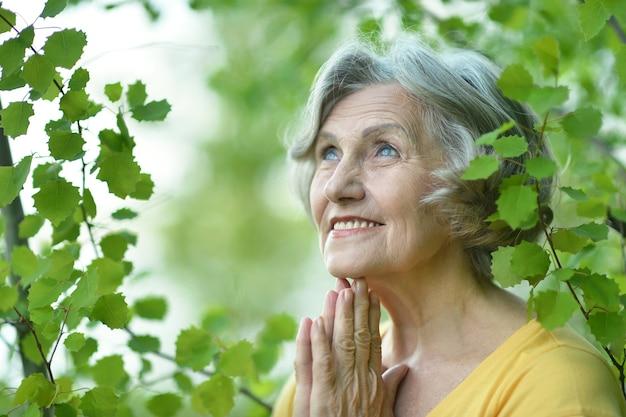 Ritratto di una donna anziana in una passeggiata nel parco in primavera