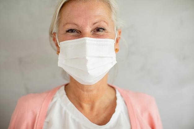 Ritratto di donna senior che indossa la maschera facciale medica protettiva per la protezione dai virus
