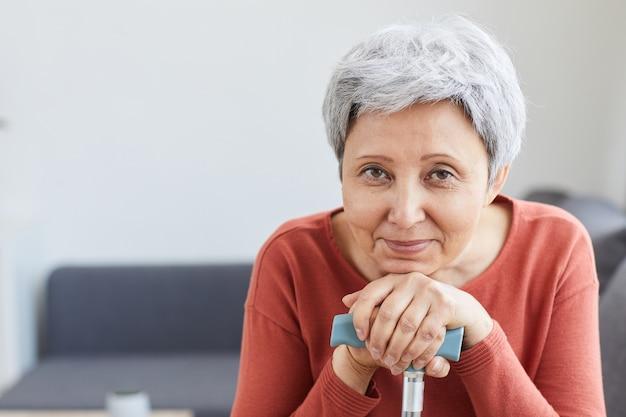 Ritratto di donna senior con i capelli grigi mentre è seduto sul divano e riposa a casa