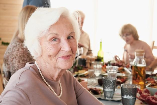 Ritratto di donna senior con i capelli bianchi alla ricerca che ha la cena con la sua famiglia al tavolo