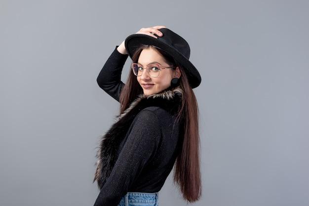 Ritratto di una donna sensuale con i capelli lunghi e un cappello nero in testa isolato su una superficie grigia