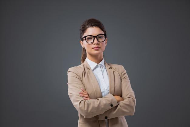 Ritratto di una seria imprenditrice adulta in piedi davanti a un muro grigio con occhiali con occhiali neri