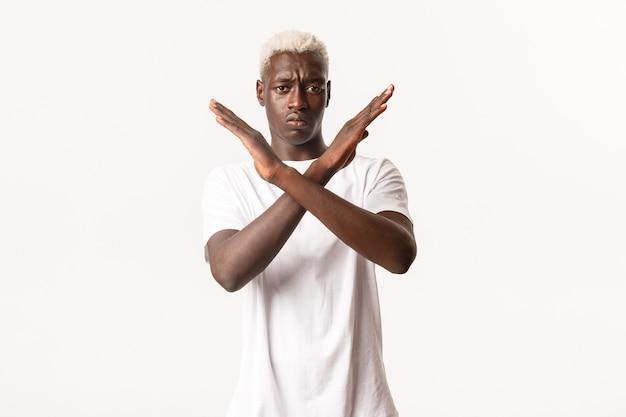 Ritratto di uomo biondo afro-americano serio, facendo un gesto trasversale per fermare qualcosa di brutto, disapprovare l'azione, vietare