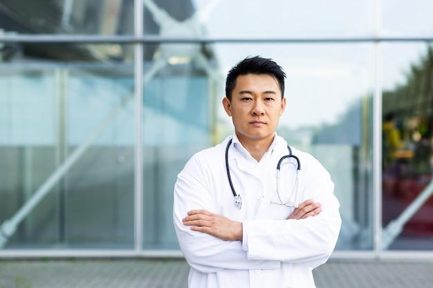 Ritratto di medico asiatico serio con le braccia conserte sullo sfondo della clinica moderna all'aperto