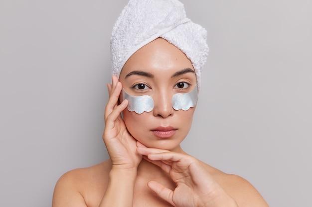 Il ritratto di una donna asiatica seria tiene teneramente le mani vicino al viso
