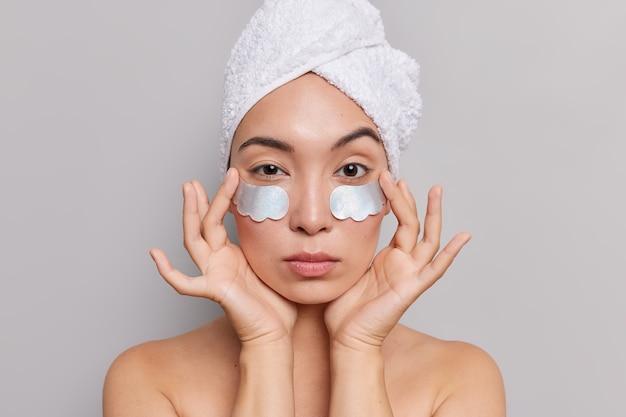 Il ritratto di un modello femminile asiatico serio e attraente gode di morbidezza della pelle dopo che le procedure termali applicano cerotti di collagene sotto gli occhi si erge sulle spalle nude su grigio
