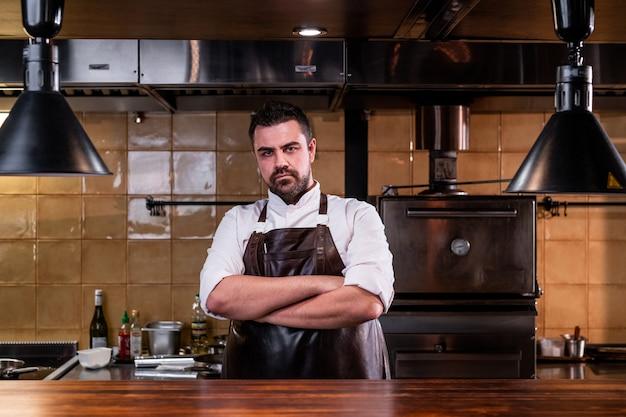 Ritratto di chef barbuto serio in grembiule di cuoio in piedi con le braccia incrociate alla cucina del ristorante