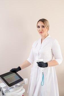 Ritratto di serio estetista in camice da laboratorio e guanti chirurgici in piedi con manico a apparecchiature di depilazione laser