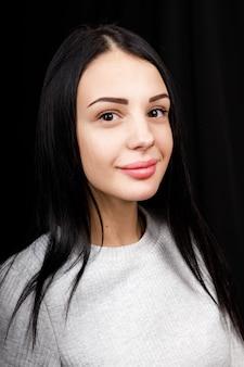 Ritratto di bella donna seria con i capelli neri, ha un trucco minimo, guarda con calma la telecamera, indossa un maglione bianco, si erge su sfondo nero, essendo immerso nei pensieri.