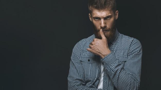 Ritratto dell'uomo barbuto brutale serio che tocca i baffi copia spazio a sinistra