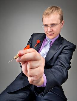 Ritratto dell'uomo d'affari serio che mira dal dardo rosso