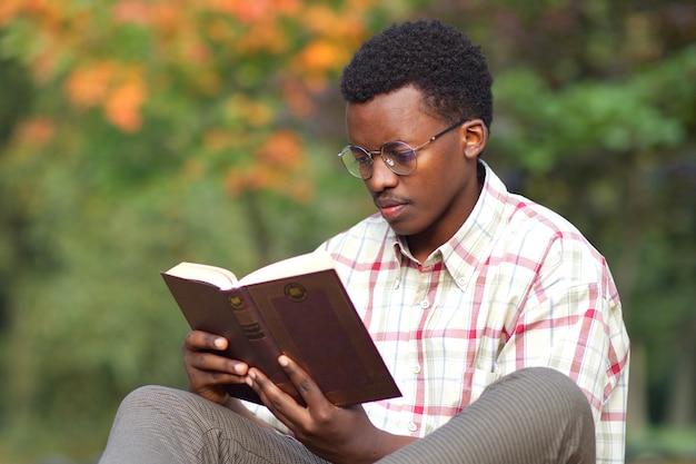 Ritratto di studente uomo intelligente afroamericano giovane concentrato serio in bicchieri e camicia leggendo un libro nel parco autunno dorato
