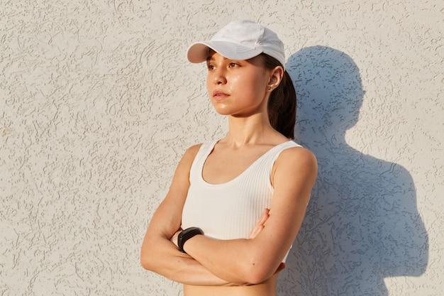 Ritratto di donna seria fiduciosa che indossa top bianco e berretto con visiera, in piedi isolato su un muro grigio all'aperto con le mani giunte, guardando in lontananza, donna sportiva dopo l'allenamento.