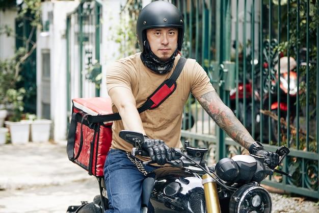 Ritratto di un fattorino serio in casco in sella a una motocicletta durante la consegna degli ordini ai clienti