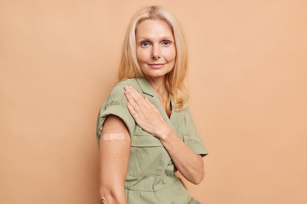 Il ritratto di una donna europea seria con i capelli biondi del trucco minimo mostra che il braccio intonacato ottiene il vaccino mentre la prevenzione contro il covid 19 guarda direttamente sul davanti indossa un vestito