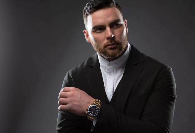 Ritratto di un uomo d'affari serio di moda con la barba vestito con un abito nero e una camicia bianca