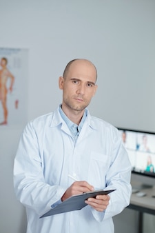 Ritratto di medico generico serio in camice bianco che scrive i dati dei pazienti nel documento