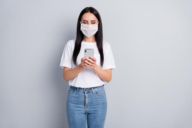 Ritratto di ragazza seria in maschera respiratoria utilizzare smartphone ricerca social media epidemia informazioni indossare jeans denim maglietta isolato su sfondo di colore grigio