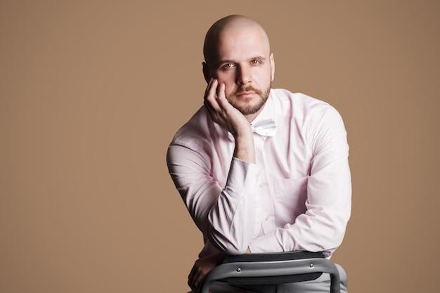 Ritratto di uomo calvo barbuto bello serio in camicia rosa chiaro e fiocco bianco, seduto sulla sedia e guardando la telecamera con la mano sul mento. foto in studio al coperto, isolata su sfondo marrone