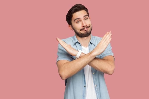 Ritratto di un giovane barbuto bello serio in camicia blu stile casual in piedi con le mani del segno x e che guarda l'obbiettivo. girato in studio al coperto, isolato su sfondo rosa.