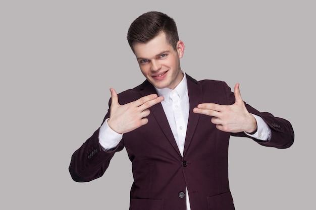Ritratto di un bel giovane serio in abito viola e camicia bianca, in piedi, che guarda l'obbiettivo con sorriso e gesto di pistola. girato in studio al coperto, isolato su sfondo grigio.