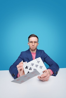 Ritratto di giocatore di carte barbuto giovane intelligente serio in vetri che si siede al tavolo e gettando le carte