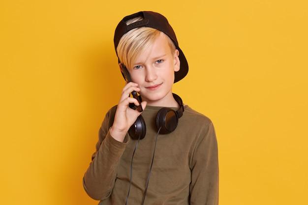 Ritratto del ragazzino serio con capelli biondi e maglione verde che parla con la sua amica o madre tramite telefono cellulare