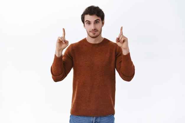 Ritratto di un uomo attraente dall'aspetto serio e sicuro con la barba che punta le dita verso l'alto, mostrando un banner promozionale