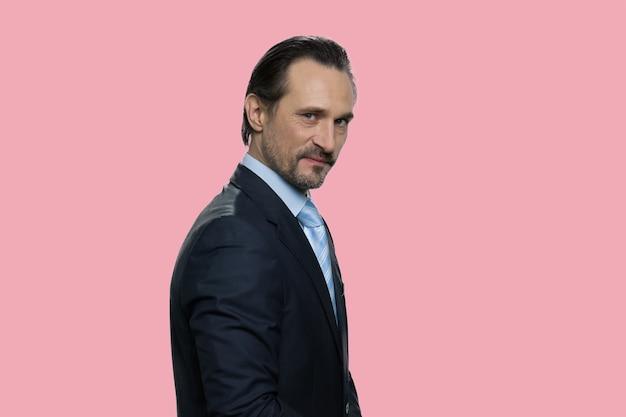 Ritratto dell'uomo d'affari maturo serio in vestito convenzionale. capo o manager isolato su sfondo rosa.