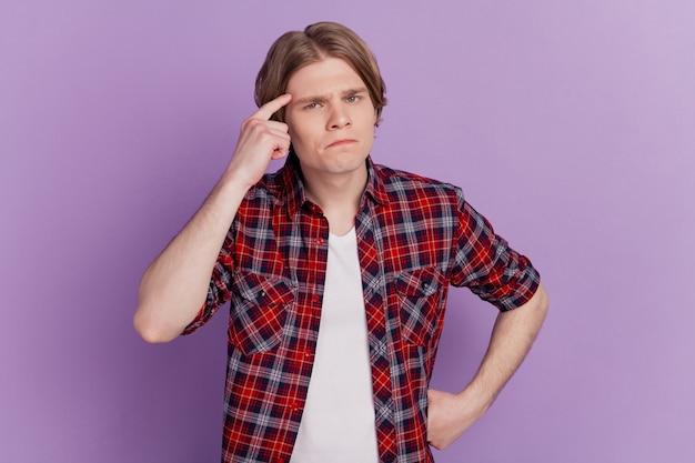 Ritratto di un ragazzo nerd serio che dimostra di sostenere che posa facendo smorfie su sfondo viola