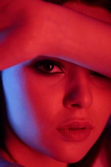 Ritratto di giovane donna seria appassionata con occhi smokey che copre la fronte con il braccio alla luce al neon