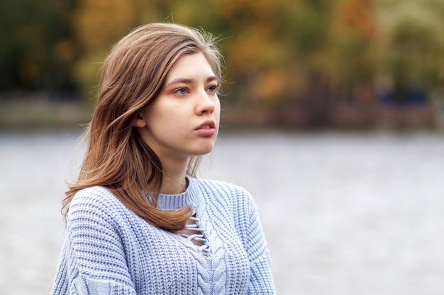 Ritratto di giovane donna premurosa pensierosa seria, adolescente in maglione che esamina la distanza sul
