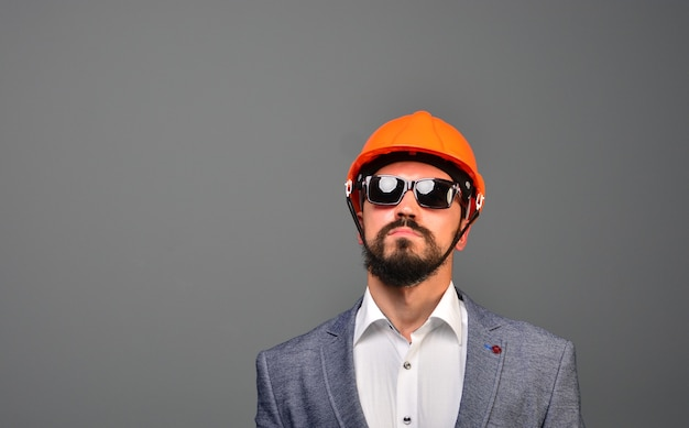 Ritratto di serio investitore immobiliare in occhiali da sole e casco di sicurezza