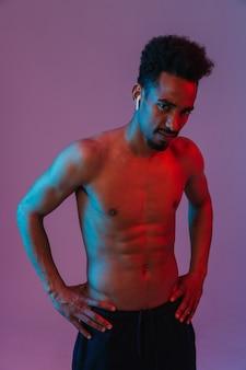 Ritratto dell'uomo afroamericano serio senza camicia che posa con i auricolari e isolato sopra la parete viola