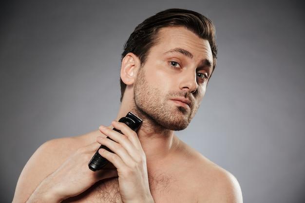 Ritratto di un uomo senza camicia serio che rade barba