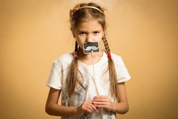 Ritratto di piccola ragazza seria che posa con i baffi decorativi