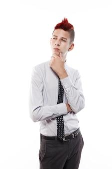 Ritratto di adolescente serio con mohawk rosso che indossa camicia e cravatta