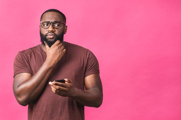 Ritratto di un ragazzo afroamericano di pensiero serio che indossa l'invio casuale e riceve messaggi al suo amante isolato su sfondo rosa. usando il telefono.